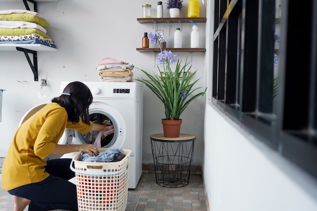 Woman in front of the washing machine doing some laundry loading clothes inside