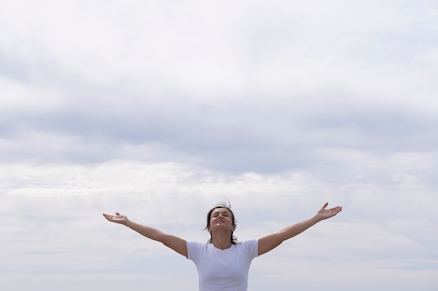 Woman in front with white shirt raising her arms to the sky