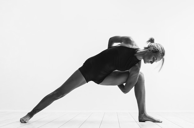 A woman in full dawn of strength, a little over forty, performs exercises from yoga. a woman has healthy well-groomed skin and hair, a toned figure and healthy shine in her eyes