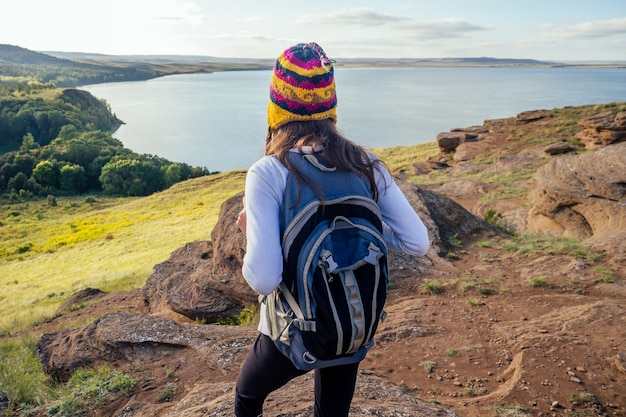 Woman in a funny hat from nepal mountain hiker with backpack hike walking on orange huge stones landscape lake and hills