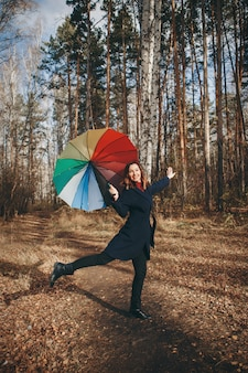 Woman funs with a colorful umbrella walks in the woods.