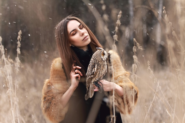 Woman in fur coat with owl hand first autumn snow
