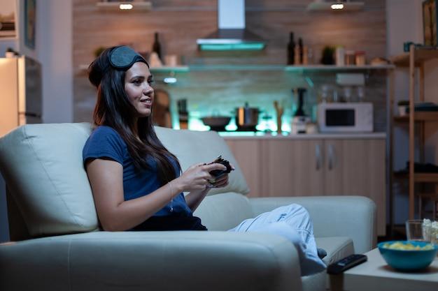 Donna giocatore che si diverte a casa seduta sul divano a giocare a un videogioco a tarda notte indossando una maschera per gli occhi sulla fronte