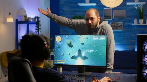 Donna giocatore che gioca a un videogioco sparatutto spaziale e combatte con il suo ragazzo per un torneo online