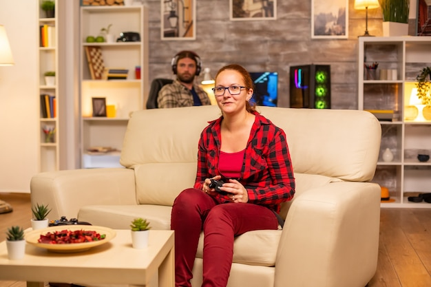 Woman gamer playing video games on the console in the living room late at night