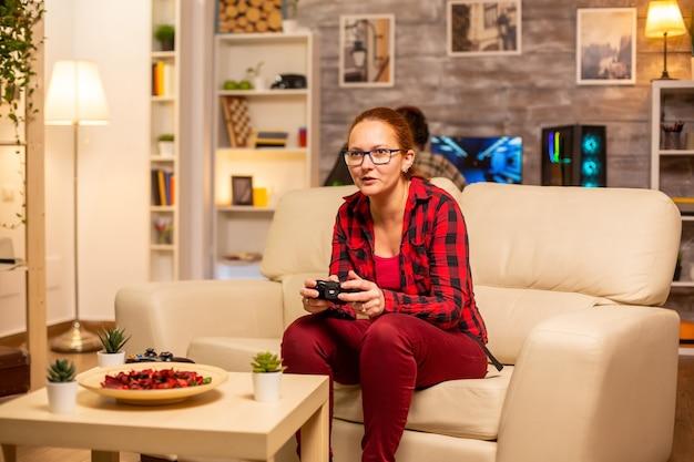 Женщина-геймер играет в видеоигры на консоли в гостиной поздно ночью