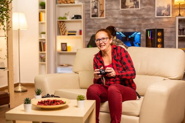 늦은 밤 거실에서 콘솔로 비디오 게임을 하는 여성 게이머