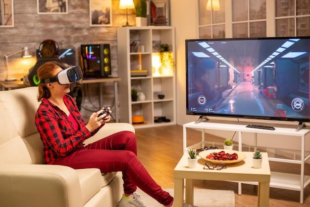Женщина-геймер играет в видеоигры с помощью гарнитуры vr поздно ночью в гостиной