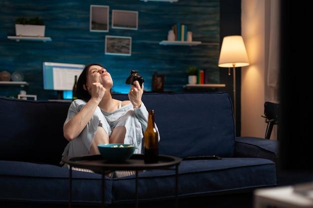 Женщина-геймер играет в видеоигры с джойстиком, сидя на диване в гостиной