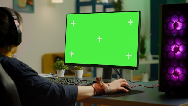 緑色の画面のモックアップ、クロマキーディスプレイを備えた強力なコンピューターでオンラインビデオゲームをストリーミングする女性ゲーマー。ヘッドセットで分離されたデスクトップストリーミングシューティングゲームでプロのpcを使用するサイバープレーヤー