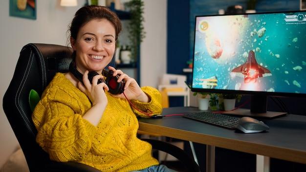 Женщина-геймер, снимающая сиденье, смотрит в камеру, улыбается и играет в чемпионате по виртуальным шутерам в киберпространстве, киберспортсмен выступает на пк в стильной комнате во время игрового турнира