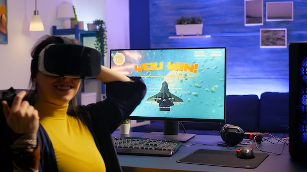 ゲームスタジオでvrヘッドセットを着用しながらスペースシュータービデオゲームに勝つ女性ゲーマー