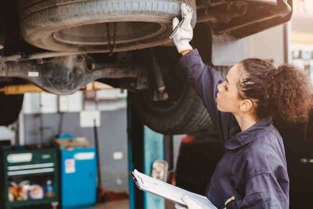 自動車サービスセンターの女性ガレージ労働者メンテナンスチェックリスト、自動車整備士の女性の作業サービスは、顧客の車をチェックして修理し、ボンネットの下の車を検査します