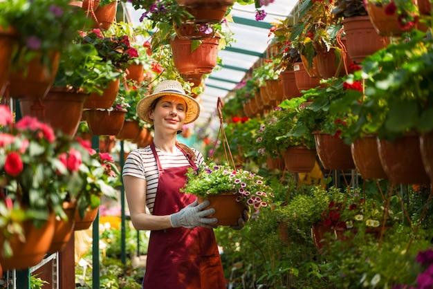 帽子と手袋をはめた女性の庭師は温室で花を扱う