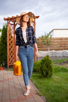 Садовник женщина в шляпе поливает растения в саду на заднем дворе