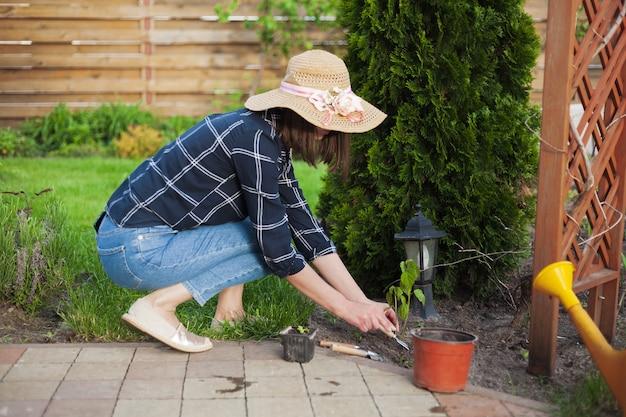 Садовник женщина в шляпе работает в саду на заднем дворе