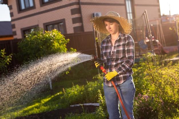 彼女の菜園のベッドに水をまく作業服の女性庭師
