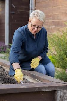 여자 정원사는 그녀의 정원에서 식물을 심기 위해 화단에서 토양을 느슨하게합니다.