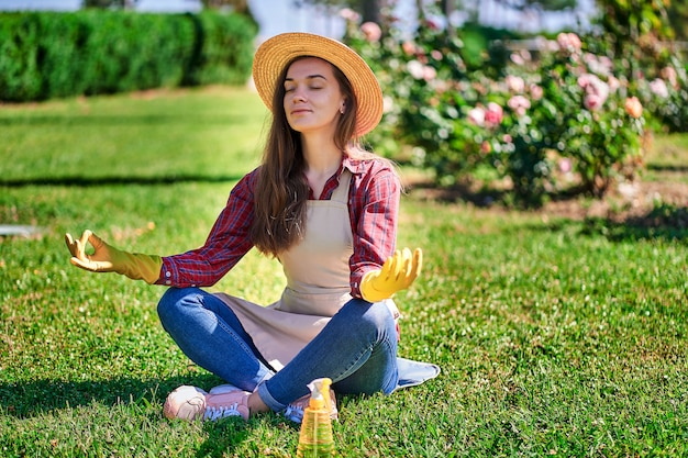 Woman gardener in lotus position relaxes and meditating in the garden