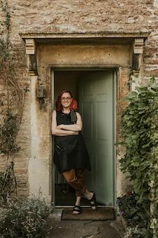 開いた緑のドアのそばに立っている女性の庭師