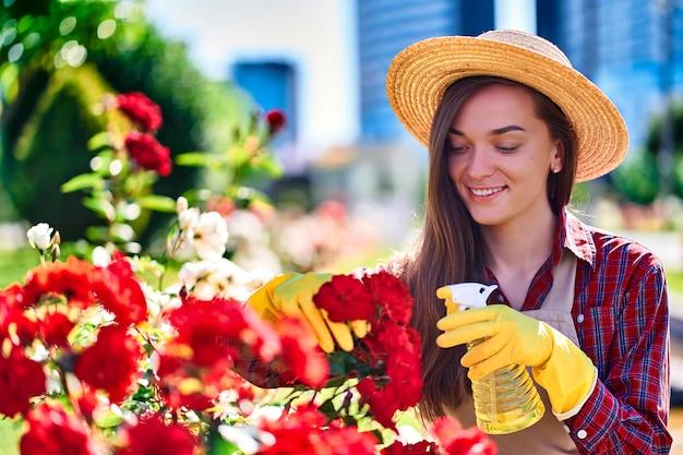 Садовник женщины используя бутылку брызга в саде