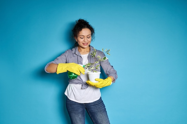 Woman gardener watering a transplanted small tree.
