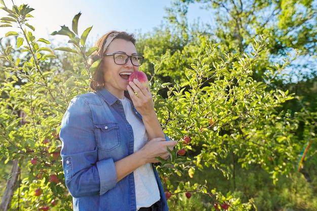Женщина-садовник с свежевыбранным красным яблоком в руке, фон - дерево с яблоками. самка ест натуральное, экологически чистое яблоко, выращенное в домашнем саду, копия пространства