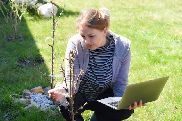 Женщина-садовник с ноутбуком, анализ урожая