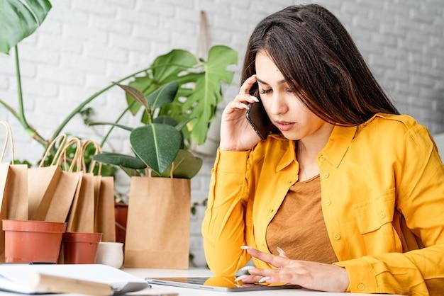 Женщина-садовник работает на цифровом планшете и звонит по телефону