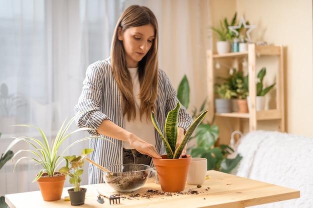 Женщина-садовник поливает растение