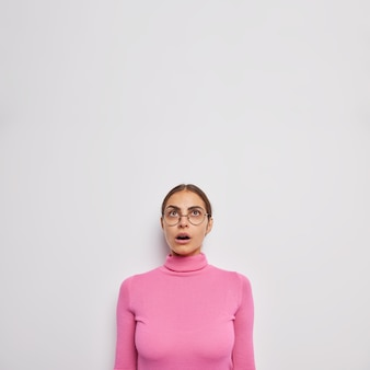 Woman gasps from wonder keeps jaw dropped hears shocking news concentrated above wears casual turtleneck and spectacles on white stares speechless