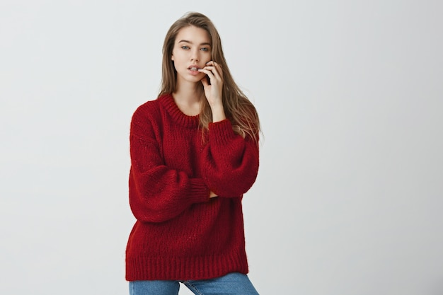 Woman gazes at attractive celebrity. portrait of modern good-looking female student with sensual expression standing in loose sweater and holding finger on lip, dreaming about person or desiring