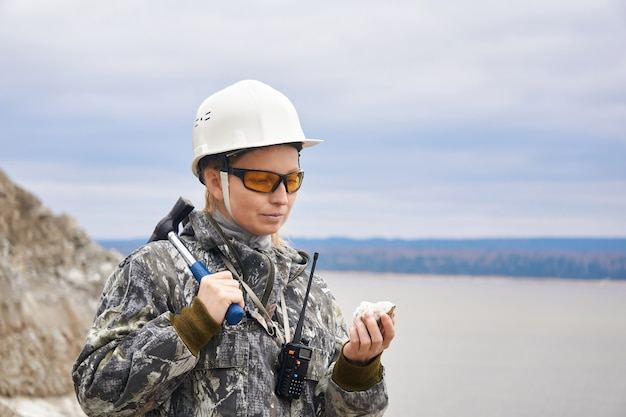 Женщина-геолог исследует образец минерала на фоне карьера на краю горы