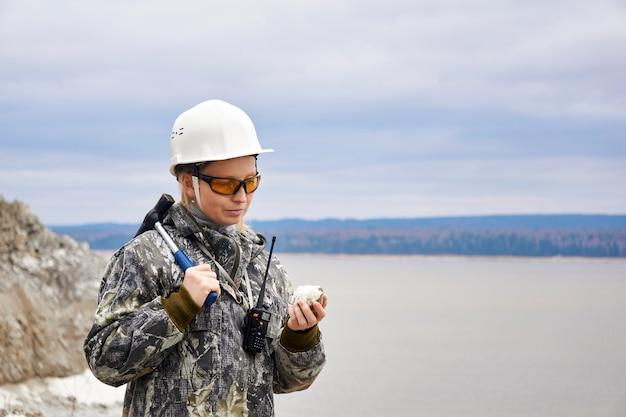 Женщина-геолог исследует образец минерала на фоне карьера
