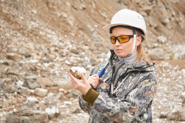 Женщина-геолог исследует образец минерала на фоне откоса карьера