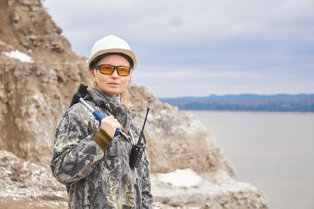 Женщина-геолог на фоне карьера на краю горы