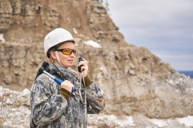 채석장 경사면을 배경으로 라디오로 말하는 여성 지질학자