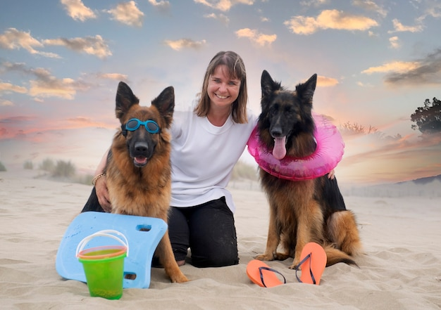 Woman and german shepherds stay on the beach