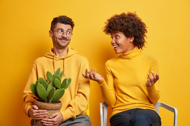 Woman gestures actively and talks with husband discuss something tries to explain her idea move in new apartment pose on chairs on yellow