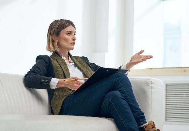 여자는 그녀의 손으로 몸짓을하고 창문 근처의 실내 소파에 앉아있다.