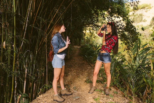 Woman gesturing while her friend taking photograph with camera