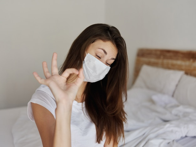 Woman gesturing with hand in medical mask in bedroom