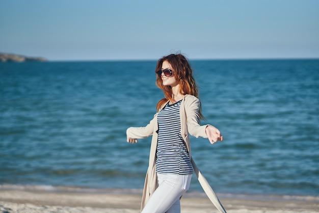 海の夏の空の近くのビーチで彼女の頭の上に彼女の手で身振りで示す女性