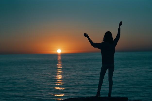 彼女の手と夕日の海の風景のビーチで身振りで示す女性