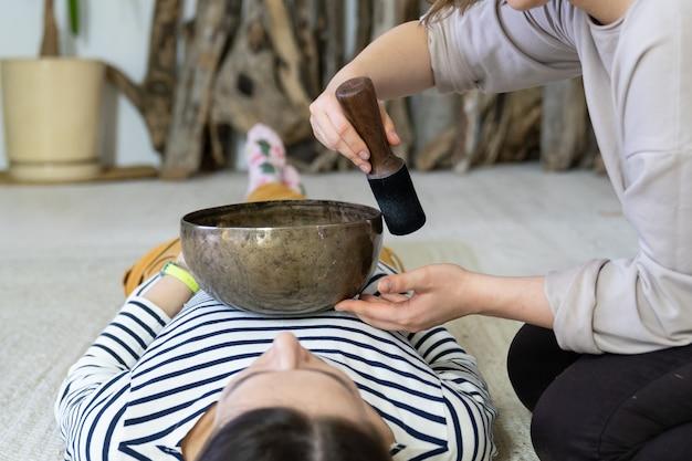 여자는 집에서 노래 그릇 치료와 에너지 사운드 마사지를받을