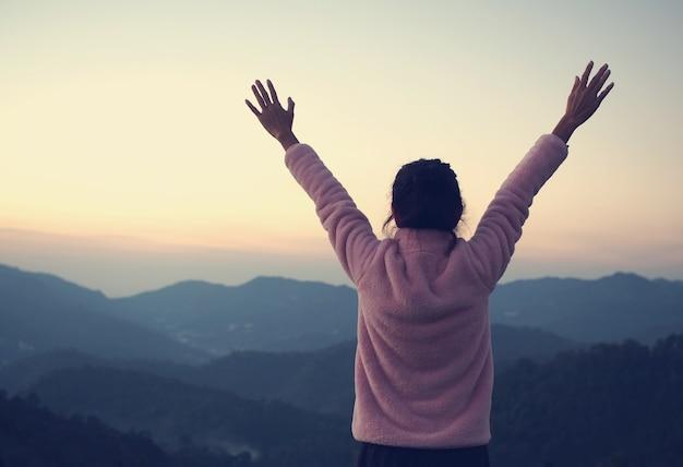 Женщина чувствует себя свободной на горе в свежих moring