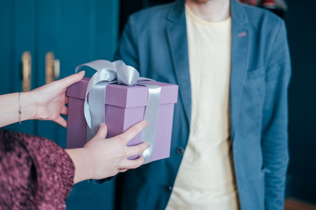 Woman get gift box with gray silver ribbon from young attracrive man on blue background
