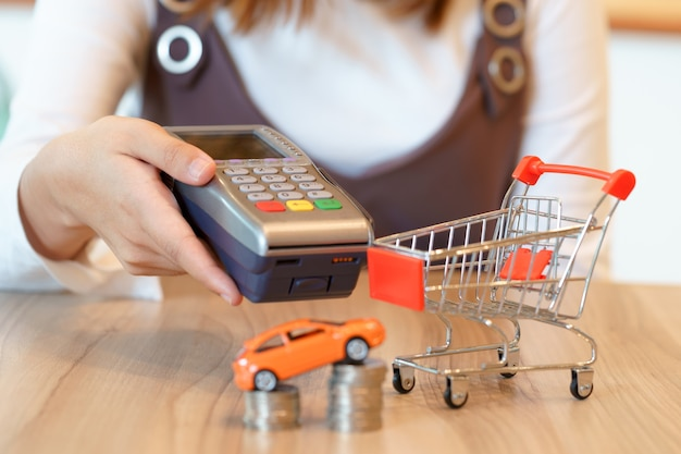 Woman get ready to paying for a new car with red shopping cart concept.