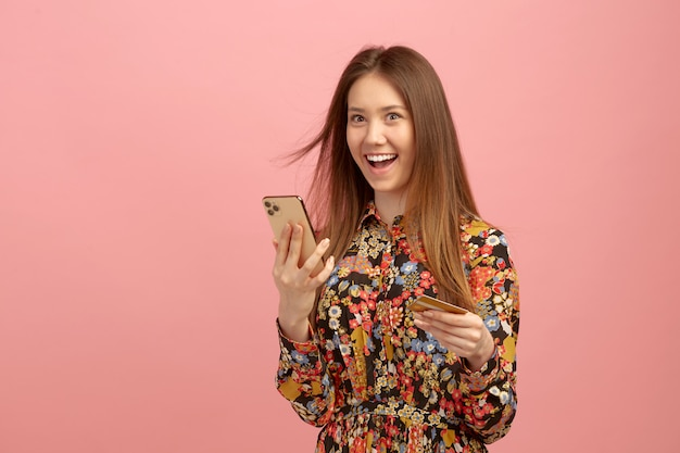 Woman gets banking service, an online purchase, using a credit card with a student offer, holds a mobile phone in hands.