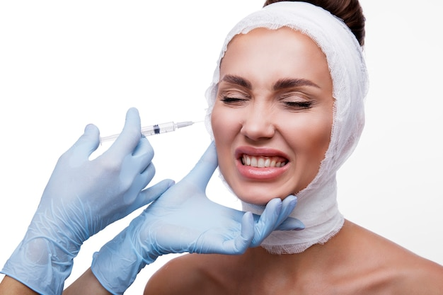 Woman gets injections beauty face bandages around the face the model shows fear and discontent